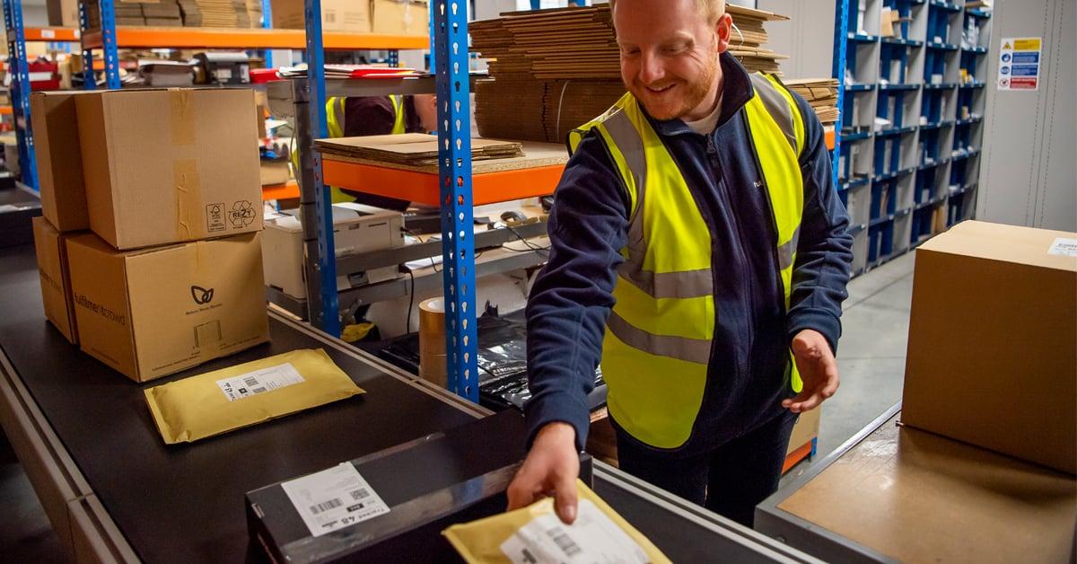 Happy warehouse worker placing parcels on conveyer belt